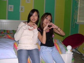 Two Asian-looking girlfriends posing together and throwing gang signs