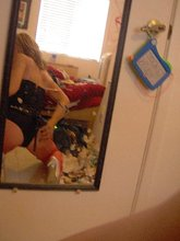 Glasses-wearing college-aged girlfriend posing in front of a mirror with her tits out