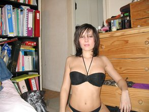 Dark-haired older wife showing off her completely naked body in a living room