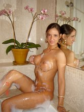 Big booty ponytailed brunette poses on a bed and naked in the bathtub
