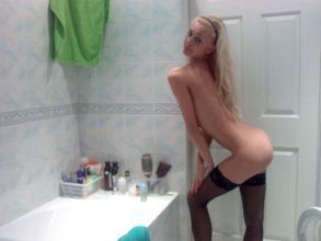 Leggy blonde dressed in black switches get-ups and gets naked in the bathroom