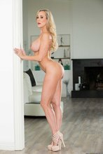 Busty blonde MILF posing with her luxurious ass turned to the camera