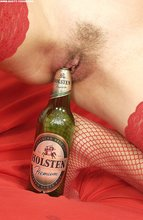Fishnets-clad short-haired blonde fucks her pussy with a beer bottle