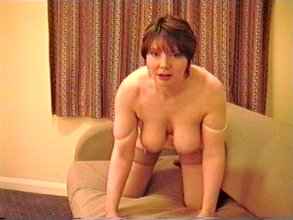 Mature redhead poses with her massive tits out on a couch and in the corner