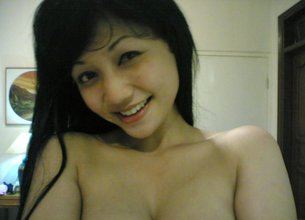 Asian bombshell with big breasts smiling and posing with her tits out