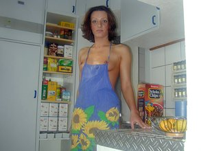 Apron-wearing brunette with curly hair flashing her tits and pussy