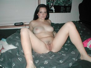 Dark-haired and pale-looking brunette spreading her slender legs on a bed