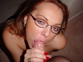Redheaded and nerdy MILF sucking a big fat cock on her knees