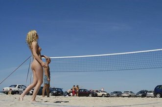 Long-legged blonde posing completely naked on a beach, playing volleyball