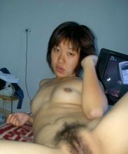 Tanned Asian hottie with a hairy pussy showing off on camera