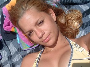 Blond-haired beauty with tan lines shows her luxurious body on a bed