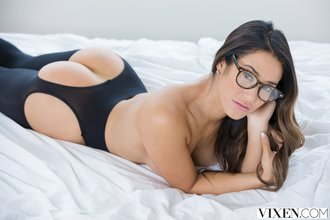 Glasses-wearing brunette in a black pantyhose doing splits on a bed