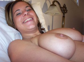 Natural breasts barely legal brunette showing her dripping pussy on a bed