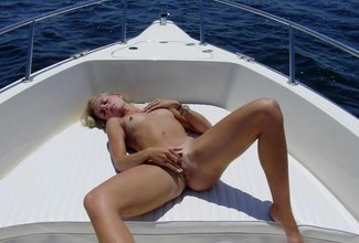 Skinny blonde with a great tan fucks another blond-haired hottie on a bed