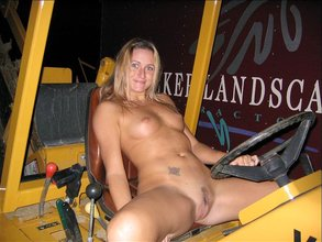 Blond-haired beauty poses naked outdoors, operates some heavy machinery