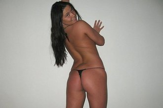 Dark-haired chick with a tanned body posing naked next to a white wall