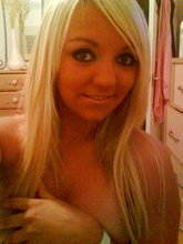 Blond-haired chav-like teen flashing her big tits in a black bra