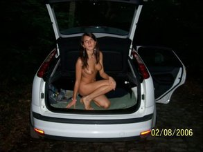 Leggy brunette with natural breasts posing on top of a car at night