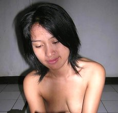 Short-haired Asian beauty poses completely naked on a cheap-looking bed