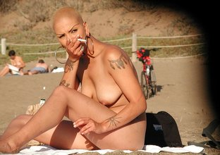 Short-haired butch-like blonde showing her naked body on a beach