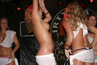 Blond-haired party girl with a tramp stamp taking her panties off on the stage