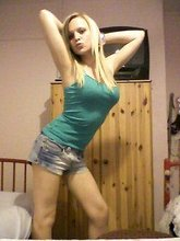 Blond-haired and skinny teen doing the duck face while stripping
