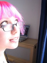 Short-haired and chubby girl with pink locks posing naked on camera