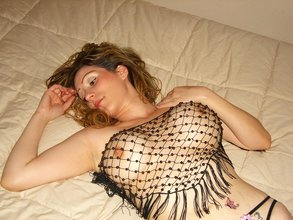 Transparent get-up busty wavy-haired brunette posing topless in the corner