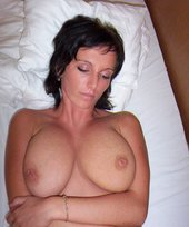 Dark-haired and barely legal hottie shows her natural big tits on a bed