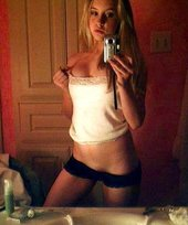 Blonde with a winning smile pulling down her panties and showing her pokies