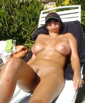Busty brunette MILF posing completely naked while sunbathing outdoors