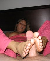 Footjob-loving blonde also enjoys sucking hairy cocks on camera