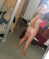Blond-haired teen in black panties showing off her beautiful ass from behind