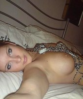 Luxurious blonde takes off her leopard print bikini on a white bed