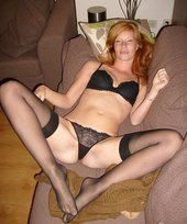 Playful redhead poses naked on all fours, she also poses in her stockings