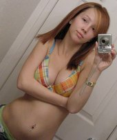Seductive teen with a smooth pussy posing topless and showing more