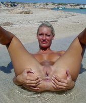 Tanned blonde with a great tan takes off her baseball cap to pose nude on a beach