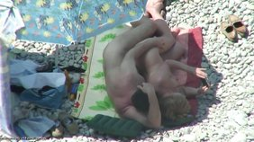 Sideways sex with a blond-haired babe on a beach