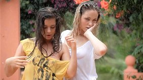 Two fun-loving girlfriends dancing around outdoors while also showering