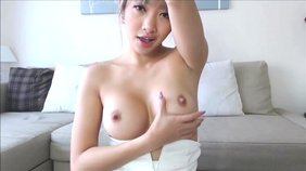Blond-haired Asian girlfriend showing off her perky tits on camera